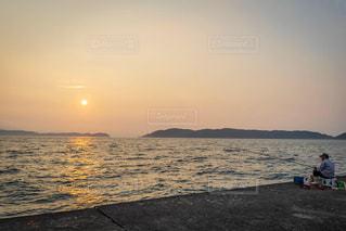 魚待つおじいちゃんと夕日の写真・画像素材[2435091]