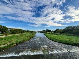 草の生いた丘を流れる川の写真・画像素材[2434780]