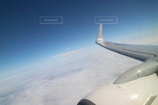 雲の上を飛んでいる飛行機の写真・画像素材[2443740]