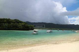 海の隣の砂浜の上に座っているボートの写真・画像素材[3557881]