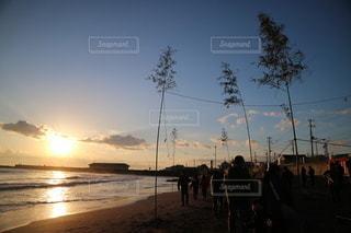 水の体の隣に立っている人々のグループの写真・画像素材[3557911]