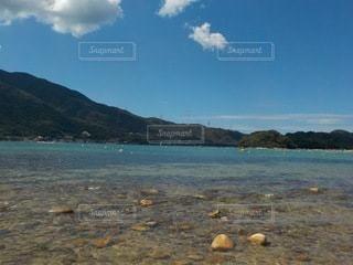 背景に山のある水の体の写真・画像素材[3557913]