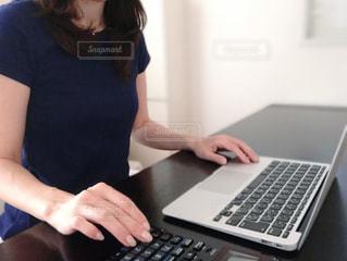 ノートパソコンと電卓で作業する女性の写真・画像素材[3329240]