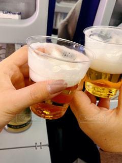 食べ物,飲み物,ジュース,飛行機,手,人物,人,イベント,ワイン,グラス,ビール,カクテル,乾杯,ドリンク,機内食,パーティー,機内,手元,飲料,プラスチックカップ,エール,ソフトド リンク