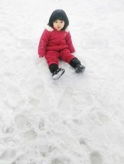 雪の中にすわっている小さな女の子の写真・画像素材[2817693]