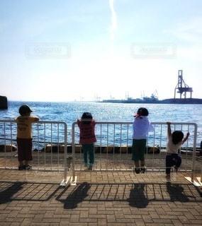 海沿いの柵に登っている子供たちの写真・画像素材[3608491]