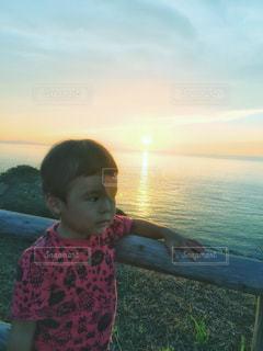 水平線に沈む夕陽と子どもの写真・画像素材[2628452]