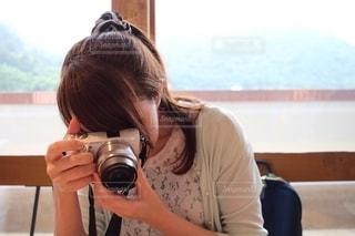 窓の前でカメラを持っている人の写真・画像素材[2499510]