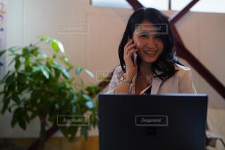 ラップトップコンピュータを使ってテーブルに座っている女性の写真・画像素材[2502235]