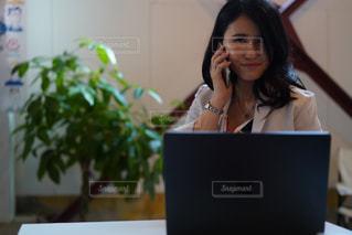 ラップトップコンピュータを使ってテーブルに座っている女性の写真・画像素材[2502246]
