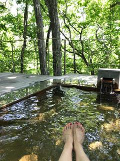 川のせせらぎが聞こえる温泉で足だけ出してる女性 - No.753748