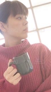 窓辺でコーヒーを飲む女性の写真・画像素材[2680603]