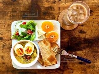 皿の上に食べ物の皿をトッピングした木製のテーブルの上のスプーンの写真・画像素材[2734946]