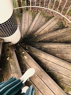 金属製のフェンスの上に座っている木製のベンチの写真・画像素材[2740151]