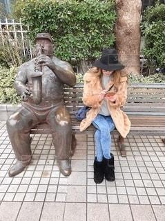 ベンチに座って楽器を吹くおじさんの写真・画像素材[2700162]
