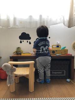 テーブルの上に座っている小さな男の子の写真・画像素材[2990518]