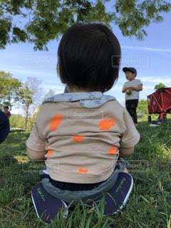 草の中に座っている小さな男の子の写真・画像素材[3086229]