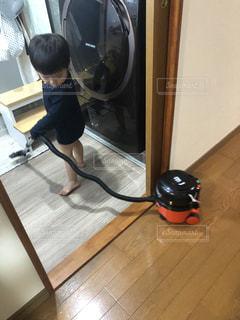 掃除機をかける小さな男の子の写真・画像素材[3133291]