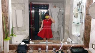 鏡の前に立つ人がカメラに向かってポーズをとるの写真・画像素材[2556755]