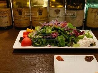 食べ物の皿とテーブルの上のワインのボトルの写真・画像素材[2737625]