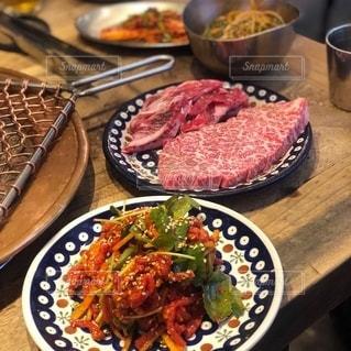 皿の上に食べ物の皿をトッピングした木製のテーブルの写真・画像素材[2737636]