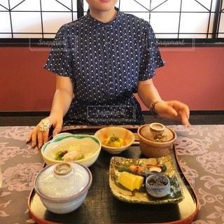 食べ物を持ってテーブルに座っている女性の写真・画像素材[2738153]