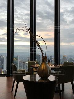 窓の隣のテーブルの上のコップの水の写真・画像素材[2738175]