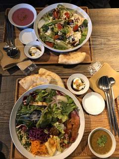 木製のテーブルの上に座っている食べ物のボウルの写真・画像素材[2888858]