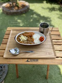 木製のピクニックテーブルの上にあるカレーの写真・画像素材[3253147]
