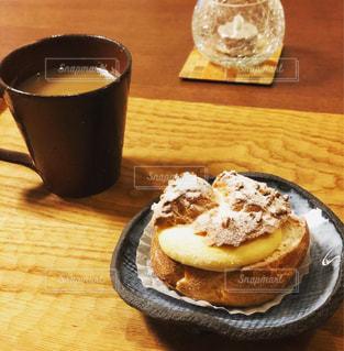 木製のテーブルの上にあるコーヒーとシュークリームの写真・画像素材[3253148]