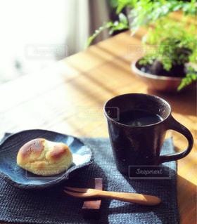 木製のテーブルの上にあるコーヒーとケーキの写真・画像素材[3253149]