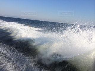 水の体の上に波に乗っている男の写真・画像素材[1387780]