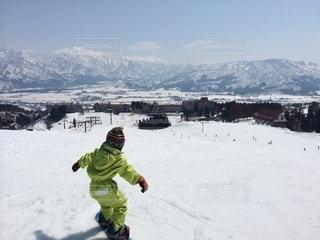 雪に覆われた山の下でスノーボードに乗っている人の写真・画像素材[2551825]