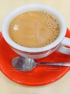 赤いお皿にミルクティーの写真・画像素材[2685011]
