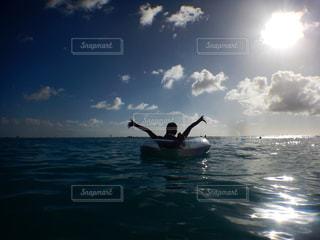 女性,1人,20代,海,空,太陽,ビーチ,雲,青,後ろ姿,波,光,逆光,ハワイ,浮き輪