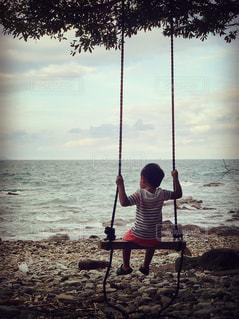水域の近くの浜辺に座っている男の写真・画像素材[2554443]