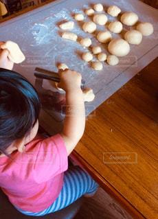 テーブルの上に座っている小さな子供の写真・画像素材[2681950]
