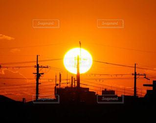 澄んだオレンジの空に沈む大きな夕日の写真・画像素材[2858815]