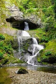 穴から流れる滝と段になってる川の写真・画像素材[4672971]