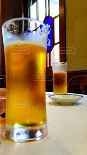飲みかけビールの向こうにステンドグラスの写真・画像素材[4675981]