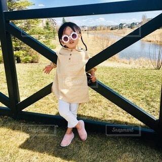 フェンスの前に立っている少女の写真・画像素材[3647394]