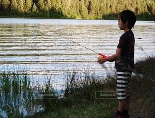 湖の隣に立っている少年の写真・画像素材[3745925]