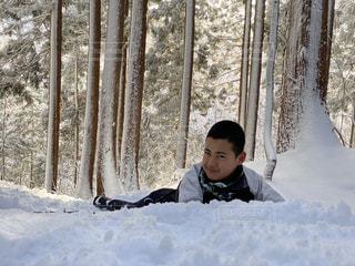 雪の中に座っている小さな男の子の写真・画像素材[2839255]