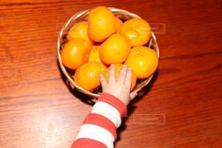 木製のテーブルの上に座っているオレンジのボウルの写真・画像素材[2870098]