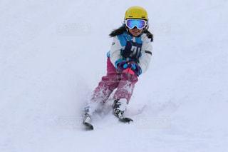 雪に覆われた斜面をスキーに乗っている少女の写真・画像素材[2944973]