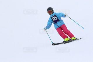 雪に覆われた斜面を滑り降りる男の写真・画像素材[2945017]