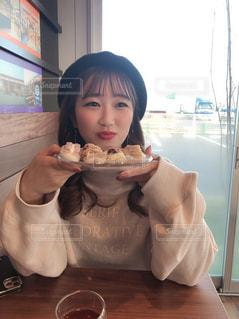食べ物を食べるテーブルに座っている小さな女の子の写真・画像素材[2975867]