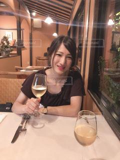 ワイングラスを持ってテーブルに座っている女性の写真・画像素材[3047528]