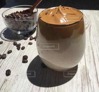 木製のテーブルの上に座っているコーヒーを一杯の写真・画像素材[3174472]