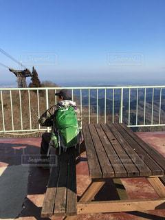 フェンスの隣のベンチに座っている人の写真・画像素材[3206397]